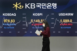 A currency trader passes by monitors showing the Korea Composite Stock Price Inde, and foreign exchange rate at the foreign…