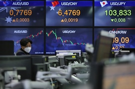 A currency trader watches monitors at the foreign exchange dealing room of the KEB Hana Bank headquarters in Seoul, South Korea…