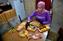 Fatima Ali prepares cheese-plate takeaway at her home kitchen in Baghdad, Iraq, Saturday, Nov. 28, 2020. After Iraq imposed a…