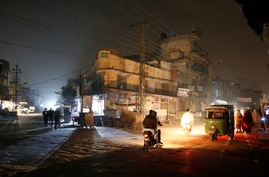 People are silhouetted on vehicles headlights on a dark street during widespread power outages in Rawalpindi, Pakistan, Sunday,…