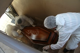 Public funeral service workers descend a flight of stairs as they remove the body of Jose Bernardino Ferreira, 77, who died…