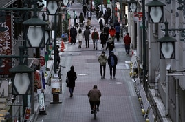 People wearing protective masks to help curb the spread of the coronavirus walk along a shopping street in Tokyo Monday, Jan…