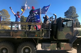 Supporters of President Donald Trump ride in the back of a truck oustside the Statehouse in Santa Fe, N.M., on Wednesday, Jan…
