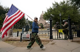 Pro-Trump supporter Connie Kirtley, of Dayton, Texas, carries a flag near the Texas State Capitol, Wednesday, Jan. 20, 2021, in…