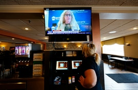 Waitress Lauren Musial watches a television briefing by Pennsylvania Health Secretary, Dr. Rachel Levine, at the Penrose Diner,…
