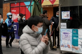 People wearing face masks to help curb the spread of the coronavirus use smartphones to scan their health code and get…