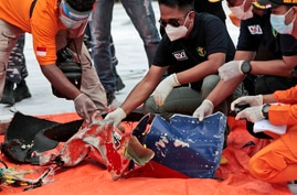 Investigators inspect debris found on the waters off Java Island around where a Sriwijaya Air passenger jet crashed, at Tanjung…