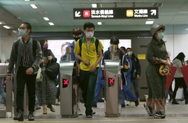 People wearing face masks to protect against the spread of the coronavirus go through gates of a metro in Taipei, Taiwan,…