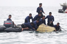 Indonesian Navy divers pull out a part of an airplane out of the water during a search operation for the Sriwijaya Air…