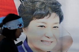 FILE - In this Aug. 29, 2019, file photo, a supporter of former South Korean President Park Geun-hye walks by the banner with…