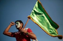 """A supporter of Shiite rebels, known as Houthis, holds a green flag with Arabic writing that reads, """"at your order, oh messenger…"""