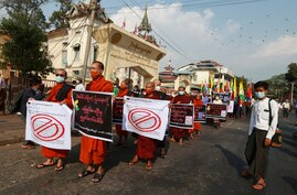 Buddhist monks hold placards as they participate in a rally protesting election results by supporters of the Myanmar military…