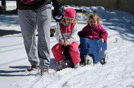 Olivia Crow, center, and sister, Elizabeth, right, are pulled through the snow by their father Craig, Monday, Feb. 15, 2021, in…