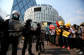 Anti-coup protesters face a row of riot police outside the Hledan Centre in Yangon, Myanmar Friday, Feb. 19, 2021. The daily…