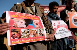 Houthi supporters hold posters as they attend a demonstration against the United States over its decision to designate the…