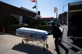 FILE - In this Friday, March 27, 2020 file photo, William Samuels delivers caskets to the Gerard Neufeld Funeral Home during…
