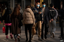 People wearing face masks to protect against the spread of the coronavirus walk at an outdoor shopping area in Beijing,…