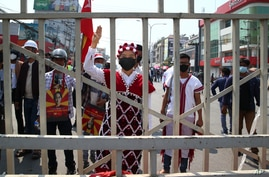 A protester wearing traditional costumes shout slogans and flash a three-finger sign of resistance during a protest against the…