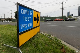A sign leading to a COVID-19 testing station in Melbourne, Australia, Thursday, Feb. 4, 2021. All competition at six Australian…