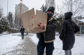 An election worker brings food to a polling station in parliamentary elections in capital Pristina, Kosovo on Sunday, Feb. 14,…