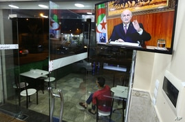A man sits outside a restaurant while Algerian President Abdelmadjid Tebboune speaks on television, Thursday, Feb.18, 2021 in…