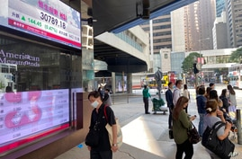 People walk past a bank's electronic board showing the Hong Kong share index in Hong Kong Monday, Feb. 22, 2021. Asian shares…