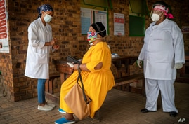 A South African woman is briefed before taking a COVID-19 test at the Ndlovu clinic in Groblersdal , 200 kms north-east of…