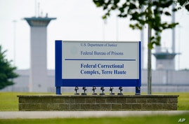 FILE - This Aug. 28, 2020, file photo shows the federal prison complex in Terre Haute, Ind. Two journalists tested positive for…