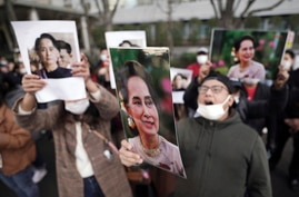 Burmese living in Japan and supporters hold pictures of Myanmar leader Aung San Suu Kyi during a protest in front of the…