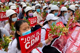 Medical students wearing face mask and hold placard as they gathers during an Anti-coup protest in Mandalay, Myanmar, Sunday,…