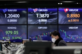 A currency trader walks near the screens showing the foreign exchange rates at the foreign exchange dealing room in Seoul,…