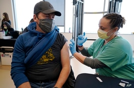 Brian Kennedy, left, a physical education teacher at Green Valley elementary School, receives a COVID-19 vaccination from nurse…