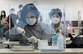 Medical workers attend a training to learn how to give coronavirus vaccine shots at the Korean Nurses Association in Seoul,…
