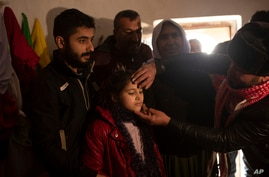 In this Feb. 12, 2020 photo, Malak Saad Dakhel, 11, is anointed by a holy man inside a Yazidi shrine as she is welcomed home by…