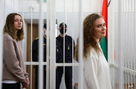 Journalists Katsiaryna Andreyeva, right, and Daria Chultsova stand inside a defendants' cage in a court room in Minsk, Belarus,…
