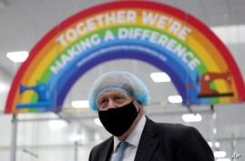 Britain's Prime Minister Boris Johnson, wearing a face mask to prevent the spread of the coronavirus, visits a PPE…