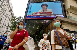 A TV screen broadcasts Hong Kong Chief Executive Carrie Lam during a news conference in Hong Kong, Tuesday, March 30, 2021…