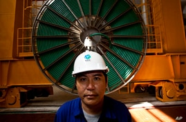 In this photo taken on Oct. 22, 2010, Laotian worker Phoumgeumh Chanthasone stands watch inside the power station of the Nam…