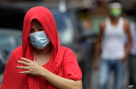 A woman wearing a protective mask walks outside a village that was placed under lockdown due to the number of COVID-19 cases…