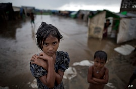 In this June 26, 2014 photo, a girl, self-identified as Rohingya, stands close to her family's tent house at Dar Paing camp for…