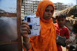 Rahima kato, a Rohingya woman displays identity cards of her family members issued by United Nations High Commissioner for…