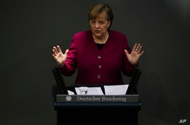 German Chancellor Angela Merkel addresses the German parliament Bundestag ahead of an European Union summit at the Reichstag…