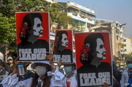 Anti-coup protesters display pictures of deposed Myanmar leader Aung San Suu Kyi in Yangon, Myanmar, Tuesday, March 2, 2021…