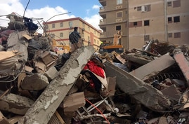 Emergency workers sift through the rubble of a collapsed apartment building in the el-Salam neighborhood, Saturday, March 27,…