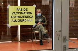 """A man waits in a vaccination center where a sign reads """"No AstraZeneca vaccinations today"""" in Saint-Jean-de-Luz, southwestern…"""