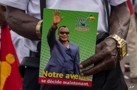 FILE - In this Friday March 19, 2021 file photo, a supporter of President Denis Sassou N'Guesso holds his photo during the last…