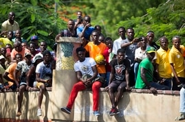 Haitian fans of the Brazil national soccer team watch the Brazil vs. Costa Rica World Cup match broadcast on a television…