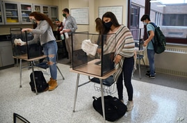 FILE - In this March 18, 2021, file photo, students in teacher Christopher Duggan's science class clean their work areas at the…