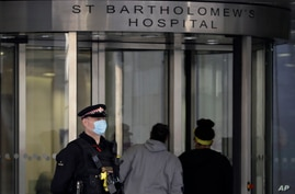 A police officer stands outside St Bartholomew's Hospital in London, Monday, March 1, 2021. Buckingham Palace says Prince…