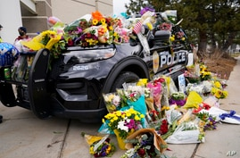 Police cruiser parked outside Boulder Police Department is covered with bouquets in tribute after an officer was one of the…